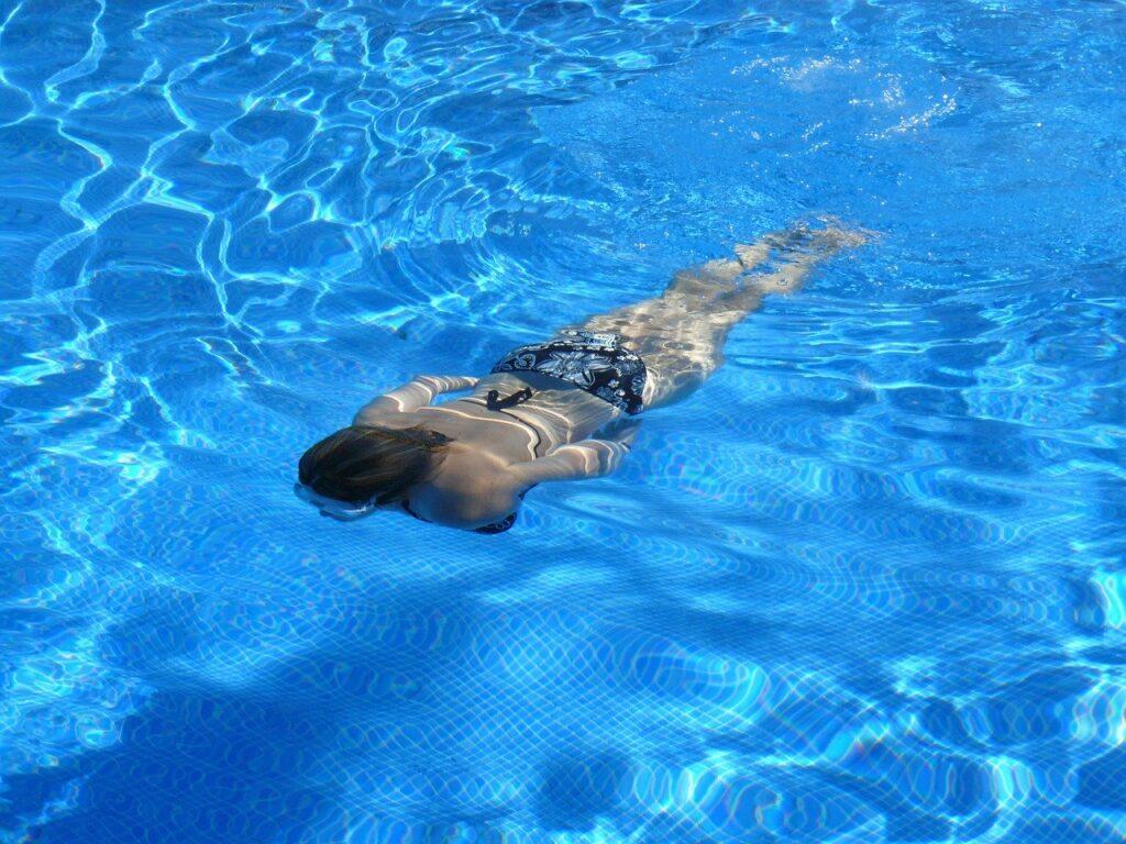 Schwimmen als Sportart für Firmenfitness: Frau im Wasser