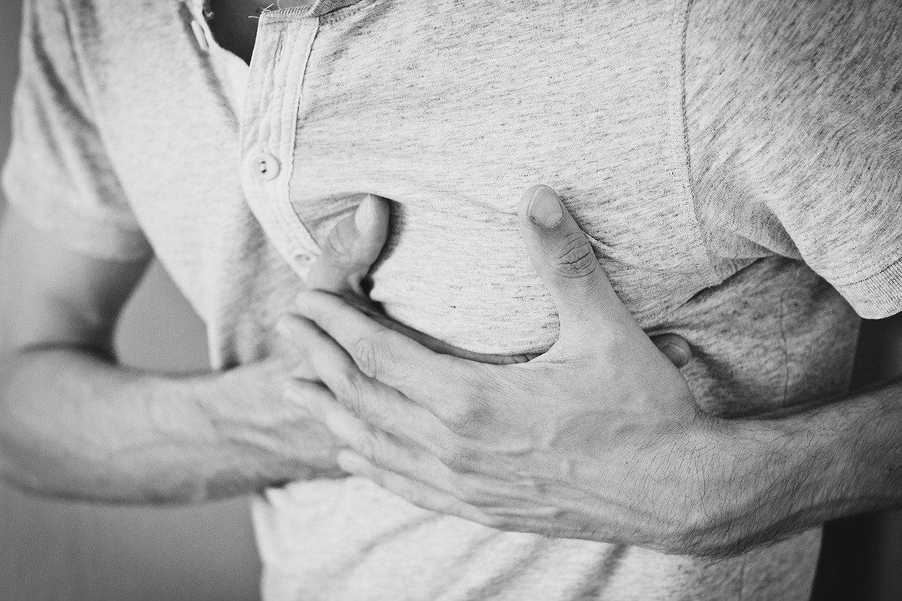 Herzgesundheit am Arbeitsplatz: Ein Mann hält sich die Brust