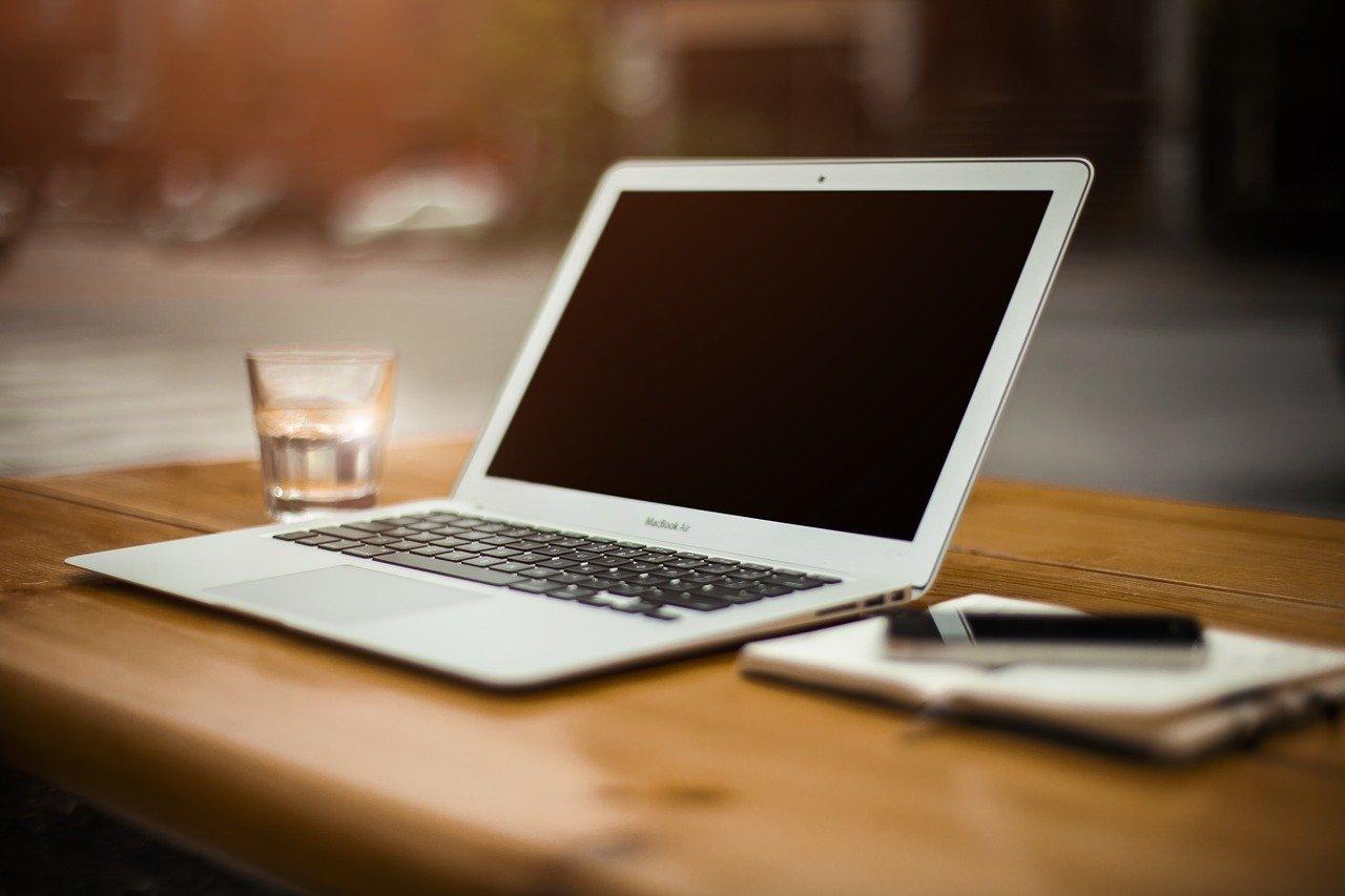 Gesundheit am Arbeitsplatz: Arbeitsplatz besteht aus Notebook, einem Glas Wasser und Notizbuch