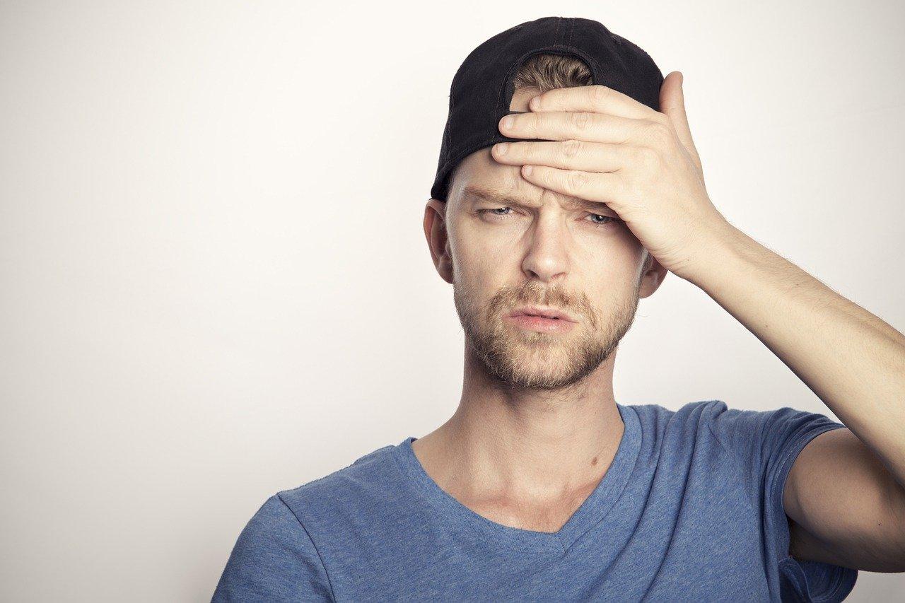 Kopfschmerzen im Büro: Mann hält sich den Kopf