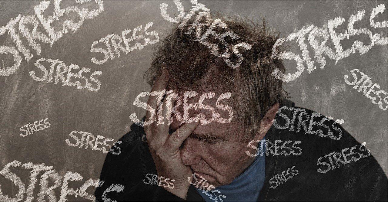 Stress am Arbeitsplatz: Ein Mann hat Stress, der um ihn bildlich herum schwirrt