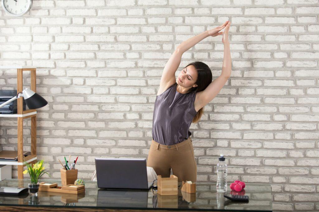 Achtsamkeitsübungen helfen den Stresslevel zu senken: Bild zeigt eine Frau , die im Homeoffice eine Achtsamkeitsübung macht